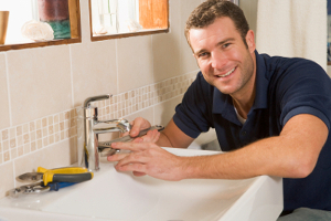 One of our plumbers fitting a basin in a bathroom