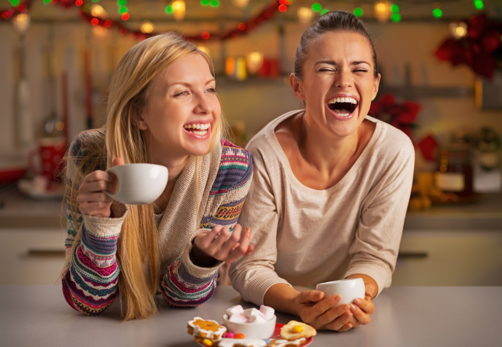 Two females in the kitchen laughing and drinking coffee